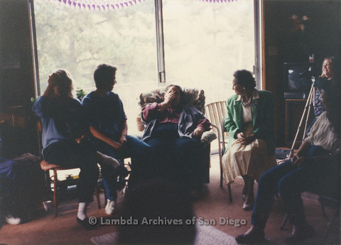 P024.368m.r.t  Edna Myers (center, face covered) seated with a group of women