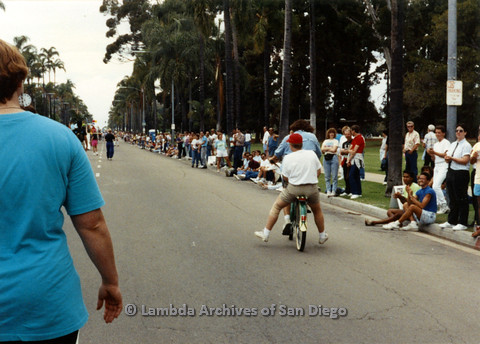 P024.464m.r.t 1990 San Diego Pride Parade: People along the street, two people on a bicycle and a woman in blue in the foreground.