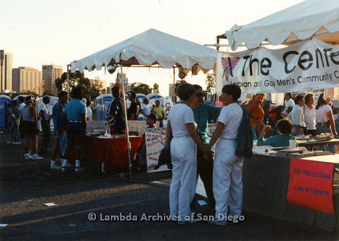 P024.521m.r.t 1990 San Diego Pride festival: People standing by The Center booth (foreground) and Club West Coast booth (background)