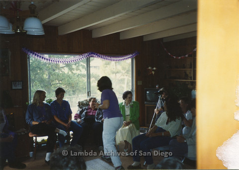P024.363m.r.t  Edna Myers (center, back in button down shirt and vest) and a group of women seated in a room.