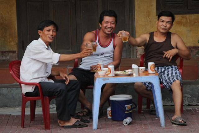 Cheers - men enjoying a roadside beer