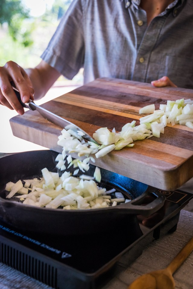 adding onions to the hot pan