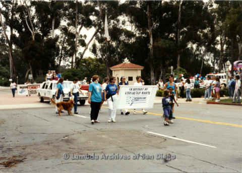 P024.421m.r.t 1990 San Diego Pride parade: (on left) Jutta Stange and (on right) Debbie Fleming holding Woman Care Clinic banner