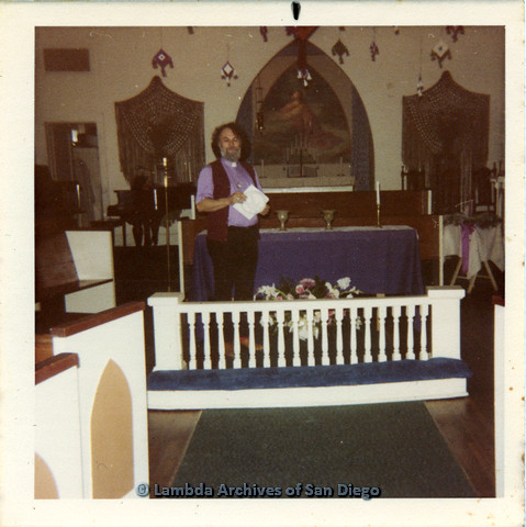 P110.060m.r.t Metropolitan Community Church: Joseph Gilbert holding papers while standing with behind knee-high barrier.