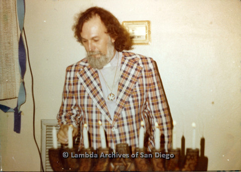 P110.032m.r.t Metropolitan Community Church: Joseph Gilbert wearing orange plaid jacket standing behind candles.