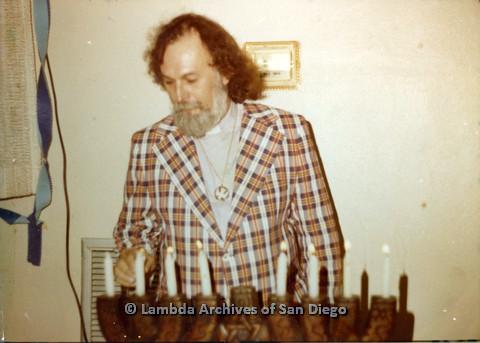 P110.032m.r.t Metropolitan Community Church: Joseph Gilbert wearing orange plaid jacket standing behind candles.