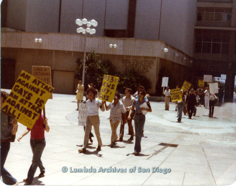 """P109.016m.r.t Civic Center Demonstration 1977: Picket line walking forward with prominent """"An Attack Against Gays Is An Attack Against All"""" sign."""