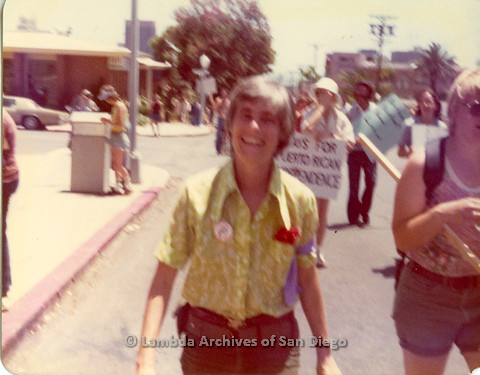P109.001m.r.t San Diego Pride Parade 1976: Woman smiling at camera in a march.