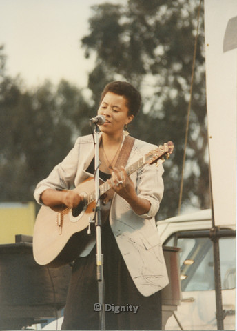 P104.149m.r.t San Diego Pride Festival 1989: Deidre McCalla playing guitar and singing into a microphone.