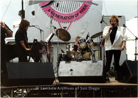 P024.394m.r.t 1989 San Diego Pride: Sue Fink in the white jacket performing on stage with Leaping Lesbians