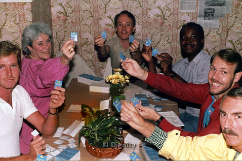"P104.044m.r.t Dignity San Diego: Stan Lewis (checkered white and blue polo), Bruce Neveu (red polo), and others smiling while holding blue boxes with words ""PLAY SAFE"""