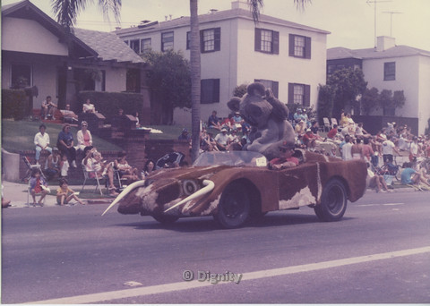 P104.134m.r.t San Diego Pride Parade: Man, woman, and koala-suit-wearing individual riding in furry brown sports car with bull horns.