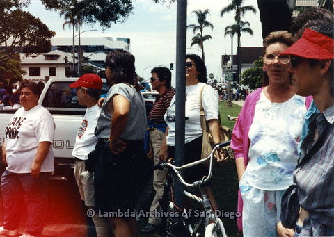 P024.471m.r.t 1990 San Diego Pride Parade: Group of people standing along the road, white truck in background. Jo-Elyn Nourie in pink to the right.
