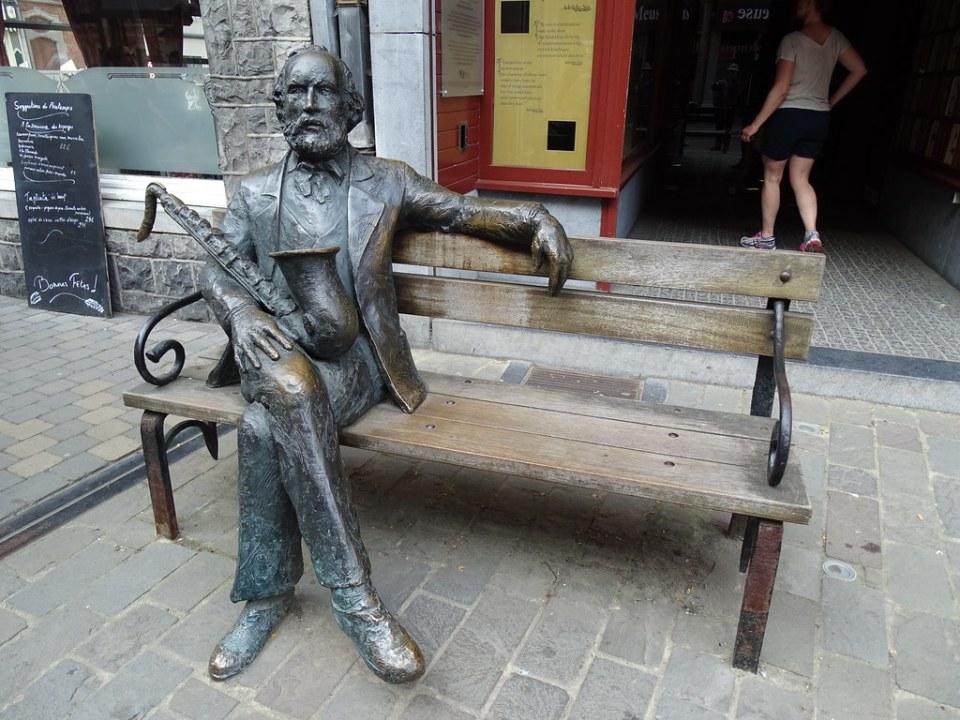 Escultura estatua Adolphe Sax sentado en un banco de Jean-Marie Mathot 2002 Dinant Belgica