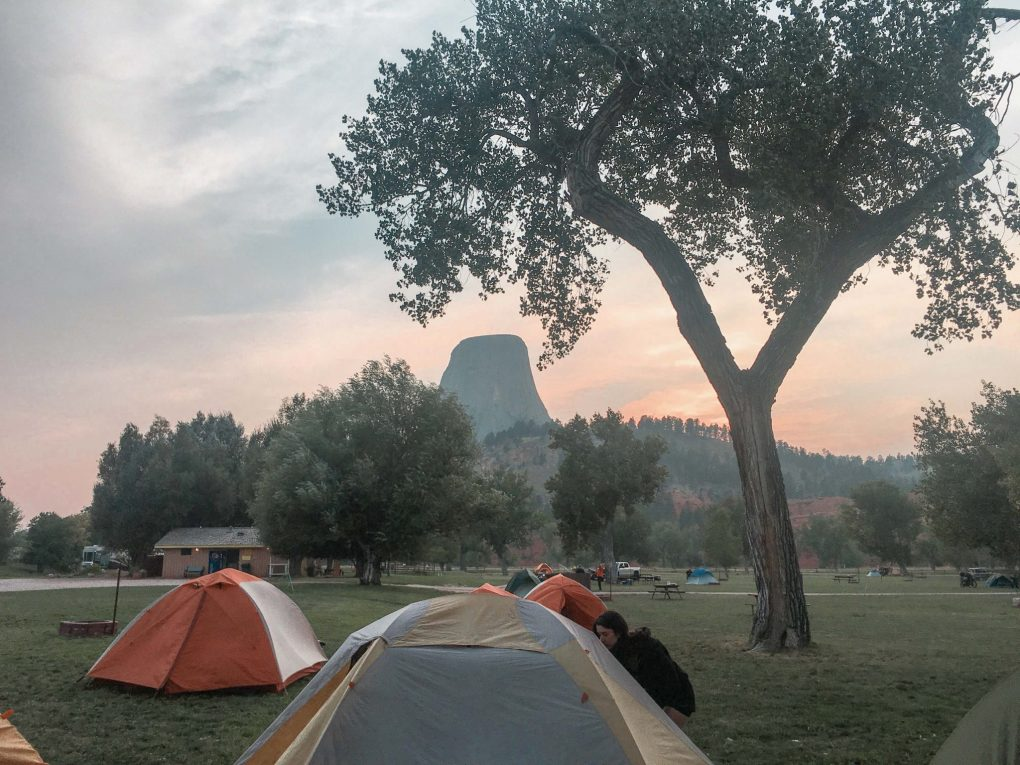 Road Trip Packing List Camping Guide Devils Tower in the background with pitched tents