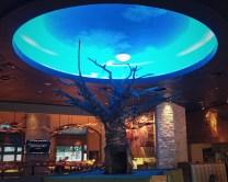 "Wire sculpture tree under LED-lit ""sky""."