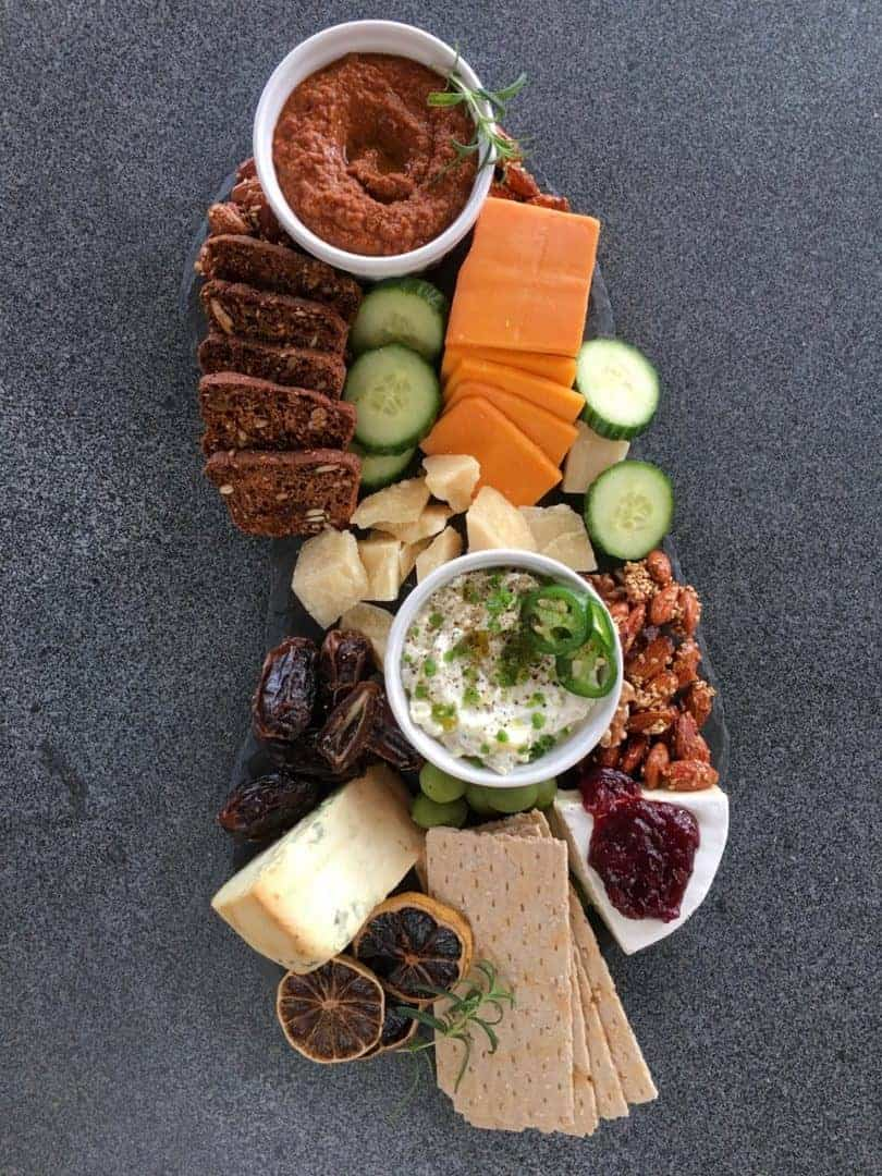 cheese, nuts, cucumber, dips on a cheese board