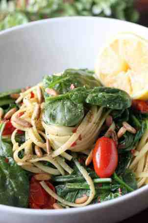 bowl of spaghetti with spinach, tomatoes and pine nuts