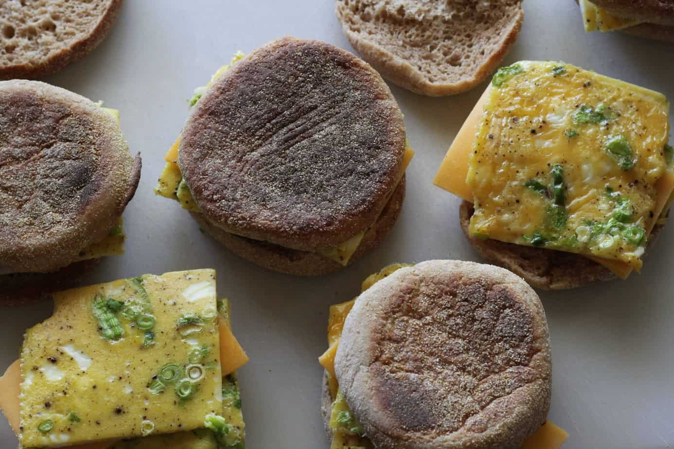 english muffins with egg and cheese on a baking sheet