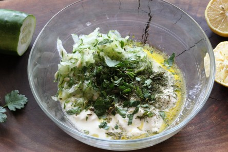 a bowl of yogurt, cucumber and herbs