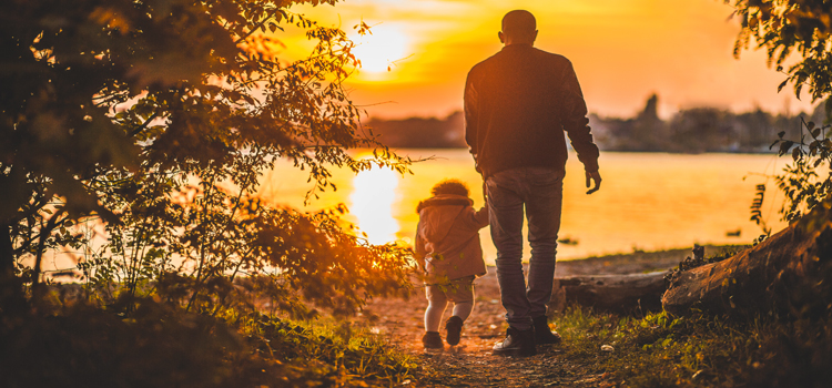 go rving, picture of a dad and daughter walking towards some water during a sunset