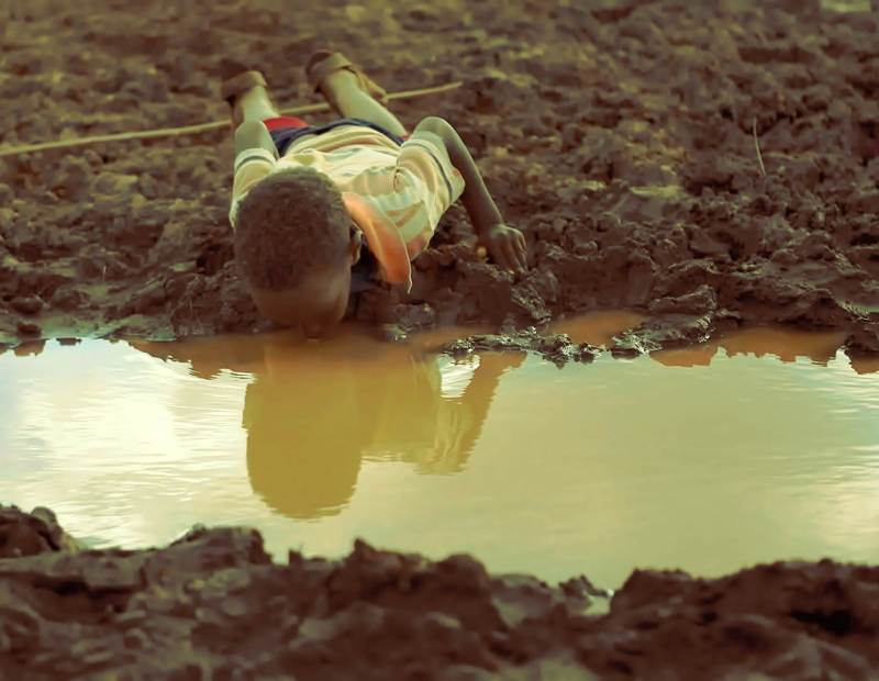 A boy drinks water from a pond in Bule Duba village in the outskirts of Moyale, near the edge of Oroma and Somali regions of Ethiopia, June 12, 2009. Copyright REUTERS/Irada Humbatova