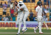 India's Ishant Sharma, left, celebrates with teammate Lokesh Rahul, center, the dismissal of Australia's Mitchell Marsh, right, during the second day of their second test cricket match in Bangalore, India, Sunday, March 5, 2017. (AP Photo/Aijaz Rahi)