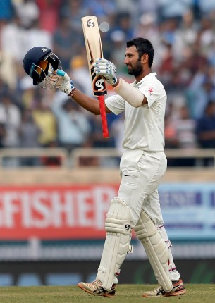 India's Cheteshwar Pujara raises his bat and helmet to celebrate scoring double century during the fourth day of the third test cricket match against Australia in Ranchi, India, Sunday, March 19, 2017. (AP Photo/Aijaz Rahi)