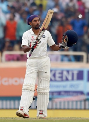 India's Wriddhiman Saha raises his bat and helmet to celebrate scoring a hundred during the fourth day of their third test cricket match against Australia in Ranchi, India, Sunday, March 19, 2017. (AP Photo/Aijaz Rahi)