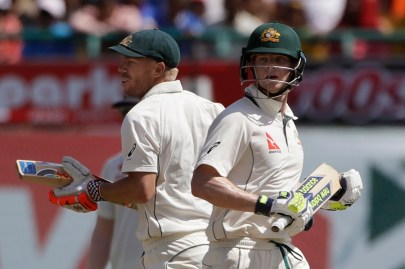 Australia's captain Steven Smith, right, and David Warner run between the wickets during the first day of their fourth test cricket match against India in Dharmsala, India, Saturday, March 25, 2017. (AP Photo/Tsering Topgyal)