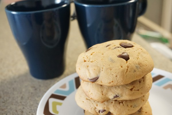 stack of cookies on a plate with mugs