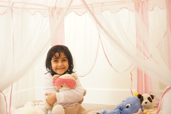kid sitting with toys in pink tent