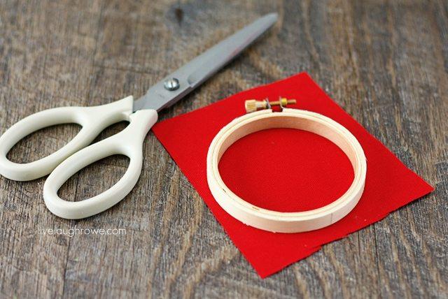 Cut fabric to fit the hoop for DIY Apple Hoop Art.