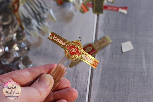 Placing the cigar band onto the chandelier crystal.