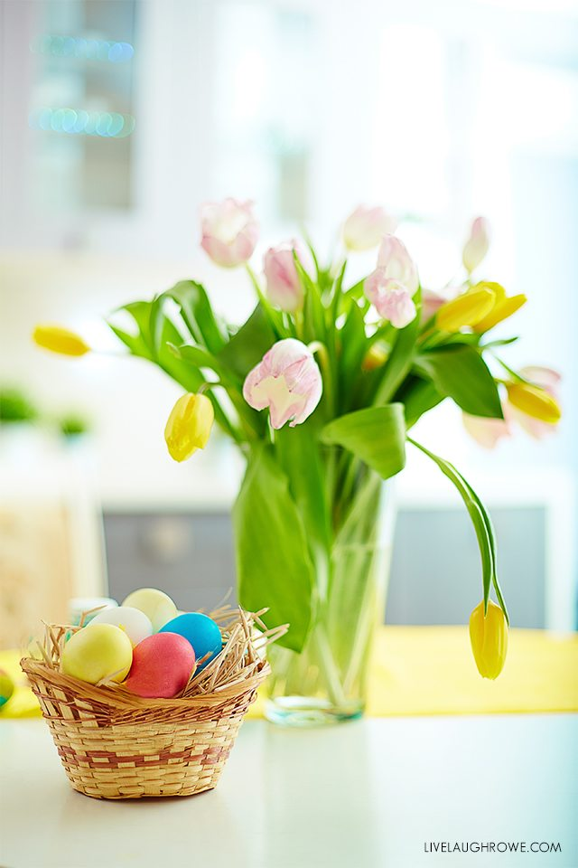 Image of colored Easter eggs in basket and bunch of tulips near from GraphicStock.com