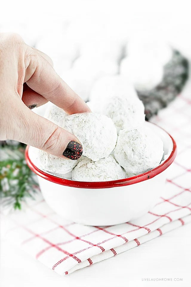 Hand reaching for a Snowball Cookie