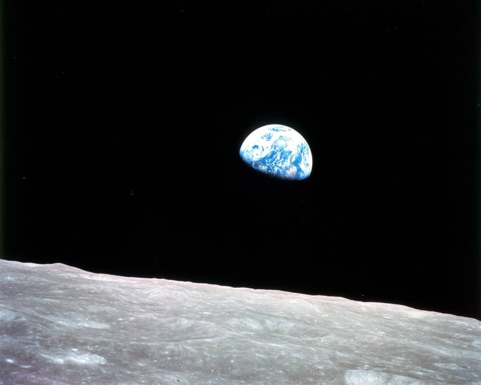 The Earth is seen rising above the lunar horizon from the Apollo 8 spacecraft.