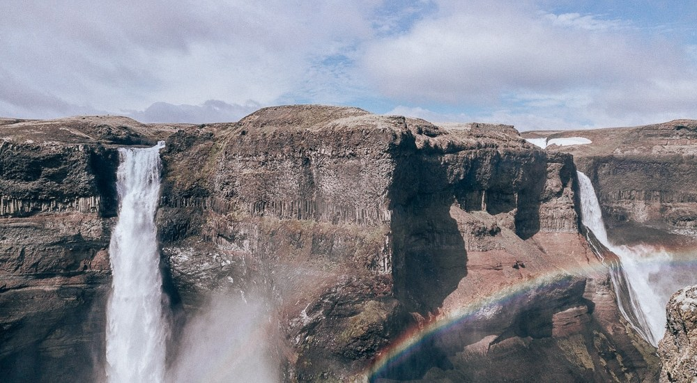 Haifoss Waterfall in Iceland with a rainbow in front of it. Find a full 6 day Iceland itinerary with a map here!