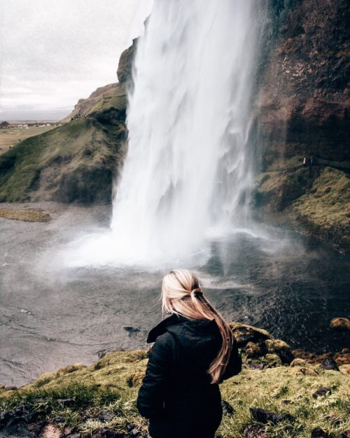 Looking at Seljalandsfoss waterfall in Iceland. Find the top 5 waterfalls in Iceland that you don't want to miss on a Ring Road road trip.