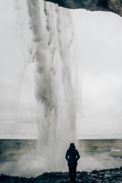 Standing behind Seljalandsfoss waterfall in Iceland and feeling the cold mist. Find the top 5 waterfalls in Iceland that you don't want to miss on a Ring Road road trip.