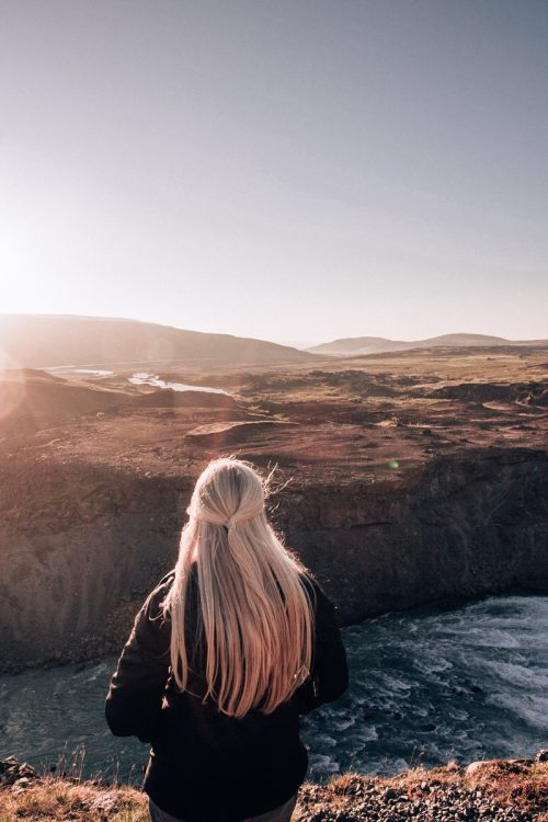 A woman watches sunset over the landscape near Aldeyjarfoss in Iceland. Find the best itinerary for summer in Iceland full of Iceland travel tips here.