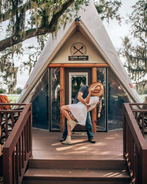 Couple glamping in Florida in front of a Westgate River Ranch teepee with cowboy hat and boots