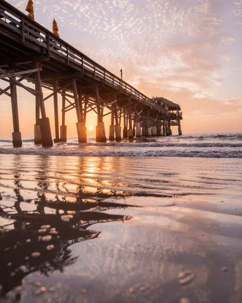 The Westgate Cocoa Beach Pier reflects in the wet sand at sunrise - find a full review of the pier and the Westgate Cocoa Beach Resort here.
