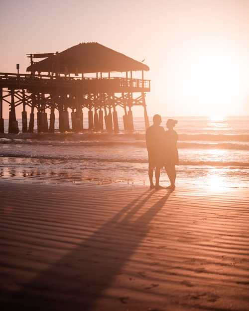 A couple on the beach at sunrise with Westgate Cocoa Beach Pier in the background. Find out why Cocoa Beach is perfect for a romantic getaway in Florida here.