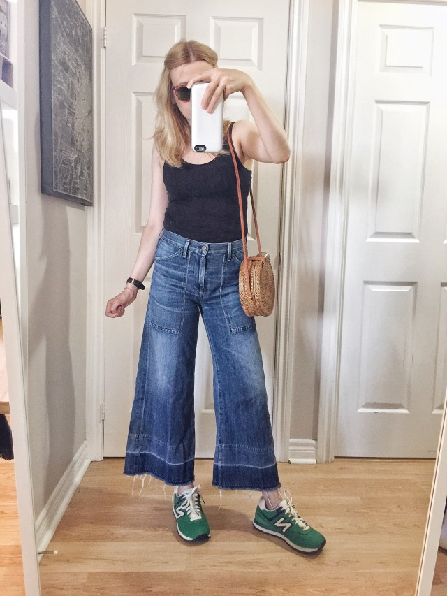 I am wearing a black tank top, wide leg cropped jeans, green sneakers, a small circle purse, and vintage Raybans