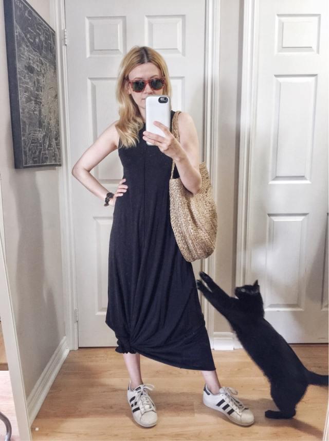 I am wearing a black maxi dress, Adidas superstars, a large circle purse, and vintage Raybans