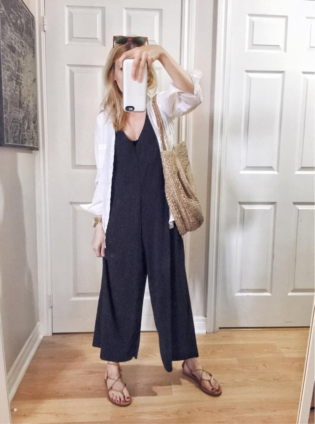 I am wearing a black jumpsuit, oversized white blouse, Madewell Boardwalk sandals, vintage Ra-bans, and a circle purse
