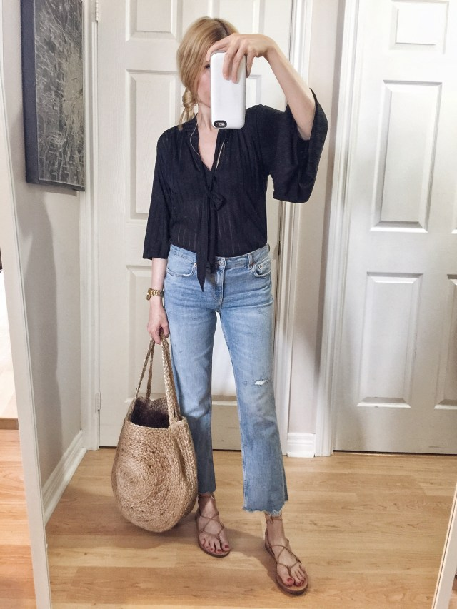 I am wearing a black i.e. neck blouse, mid rise cropped jeans, Madewell Boardwalk sandals, and a large woven purse.