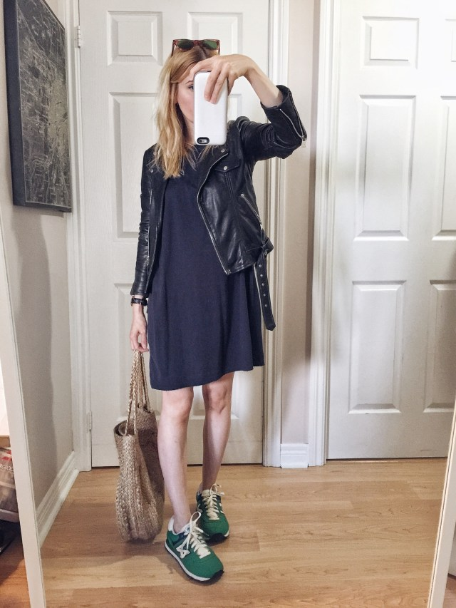 I am wearing a basic black t-shirt dress, a leather jacket, Green New Balance sneakers, and a large woven circle bag.