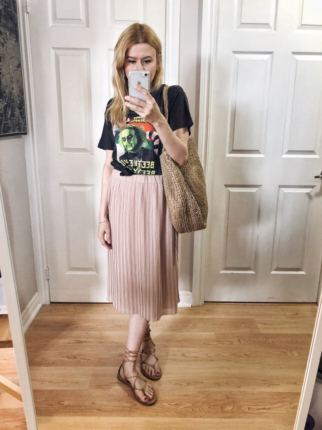 I am wearing a Beetlejuice t-shirt, pink pleated skirt, a large woven bag. and Madewell Boardwalk Sandals.